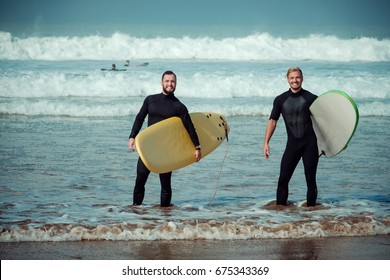 Surfer beginner and instructor on a beach with a surfboards