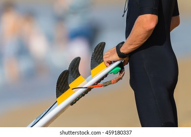 Surfer Board Fins Surfer wetsuit surfboard fins equipment closeup unidentified.