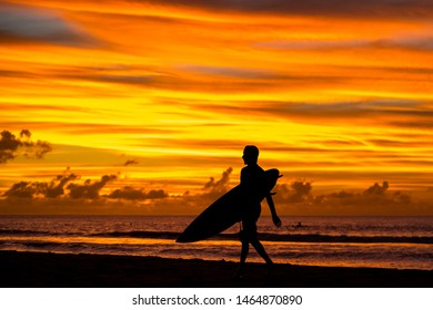 A surfer with a board returns from the ocean amid an incredible sunset. Mauritius, Indian Ocean