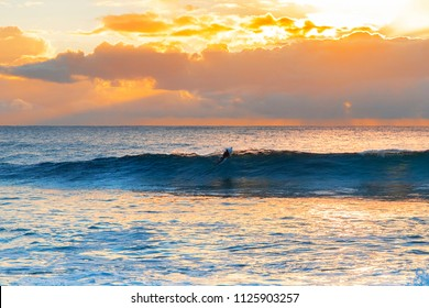 Surfer breaking through a wave at sunrise