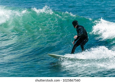 Surfer in California surfs large wave in beautiful blue water at beach