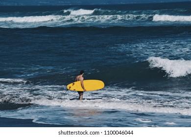 Surfer at Canggu beach in Bali Indonesia