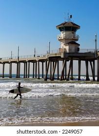 Surfer carries his surfboard at Huntington Beach Pier.