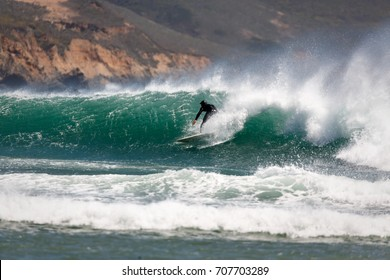 Surfer catches a wave with good strong offshore breeze behind it