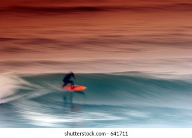 Surfer catching the afternoon wave in the stormy weather. Motion blur makes the shot dynamic.
