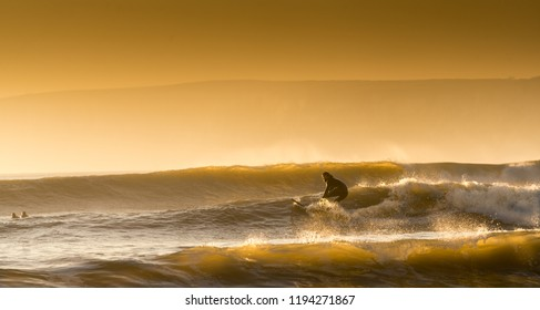 Surfer catching the last waves before sundown