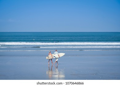 surfer couple carrying surfboards walking on kuta beach bali with denpasar behind