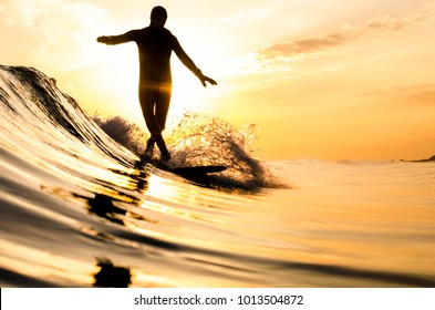 A surfer cross-stepping on a longboard in New York during a small winter swell during sunset.