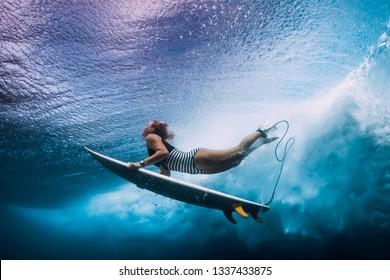 Surfer dive underwater. Surfgirl dive under big wave