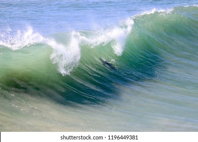 Surfer duck diving through a large wave