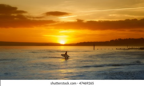 Surfer finishing for the day as the sun sets