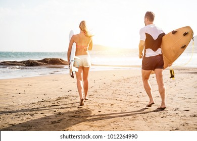 Surfer friends running with boards on the beach - Young sporty couple having fun in summer vacation - Travel, holidays and healthy lifestyle concept - Focus on bodies