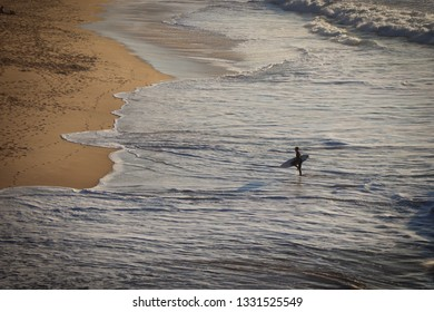 Surfer get out of the sea in a Amazing sandy beach at the sunset. Portugal