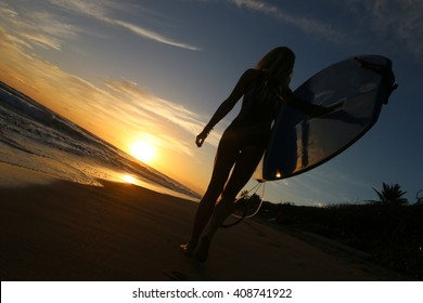 Surfer girl in bikini with surfboard walking on the beach at sunrise