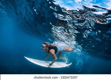 Surfer girl dive underwater. Surfer dive under big wave