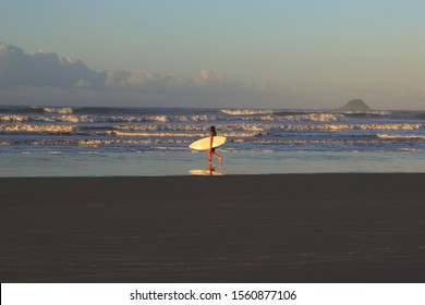 Surfer girl with her board going to the sea. Black suite and white surf board.Ocean with white waves and mountains in the background. Riviera, Bertioga, Brazil