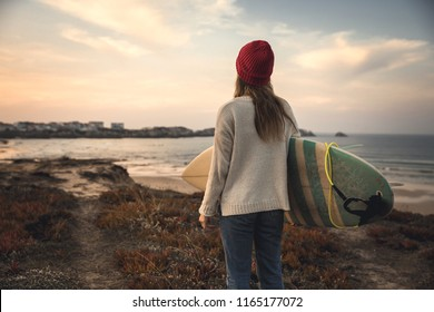 Surfer girl near the coastline with her surfboard searching for waves