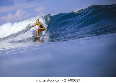 Surfer girl on Amazing Blue Wave, Bali island.