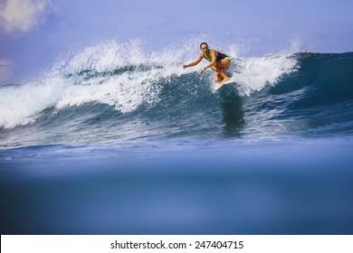 Surfer girl on Amazing Blue Wave, Bali island.