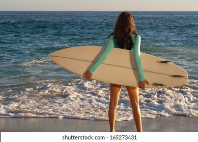 Surfer girl on the beach - Female surfer standing on the beach surfboard in hand with the ocean in the background.