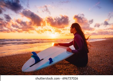 Surfer girl on sand beach with surfboard at warm sunset or sunrise. Surfer women and ocean