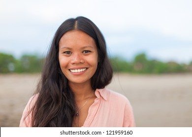 surfer girl posing on the beach and smiling