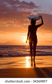surfer girl with surfboard at sunset beach in maui hawaii