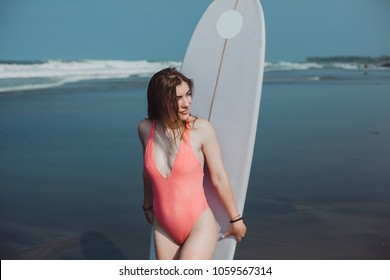 Surfer girl surfing looking at ocean beach sunset. Beautiful sexy female bikini woman looking at water with standing with surfboard having fun living healthy active lifestyle. Water sports with model.