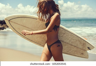 Surfer girl walking with board on the sandy beach. Surfer female.Beautiful young woman at the beach. water sports. Healthy Active Lifestyle. Surfing. Summer Vacation. Extreme Sport. Tattoo woman, Bali
