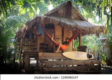 surfer in hammock at tropical  beach cottage with palm trees and surfboard