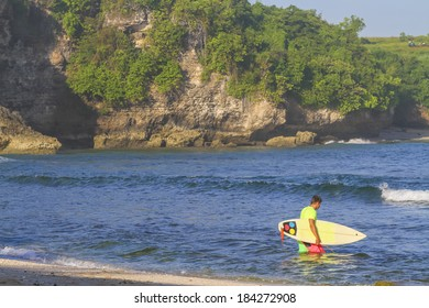 Surfer with his surfboard at the Balanfan beach.Bali.Indonesia.
