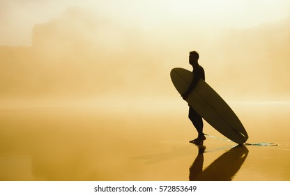 Surfer holding his surfboard and looking for waves on a misty urban beach. Outdoor beach water sport and surf lifestyle.
