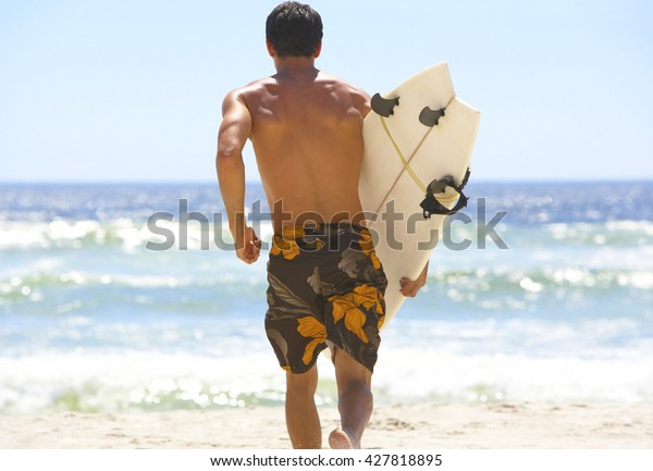 Surfer holding a surf board on tropical beach