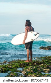 The surfer is holding a surfboard on the Indian Ocean shore