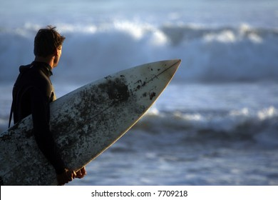 A surfer holdng his board and checking out the waves
