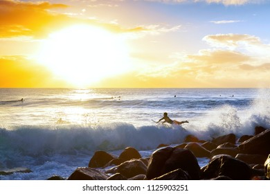 Surfer jumping into the ocean waves from the rocks at Burleigh Heads Gold Coast, with sunrise in the horizon.