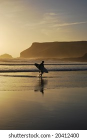 A surfer leaves the surf as the sun sets at Polzeath Beach in Cornwall, UK.