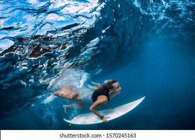 Surfer make duck dive underwater. Surfgirl dive under big wave