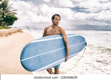 Surfer man going surfing on maui beach hawaii, usa. Professional male athlete carrying blue surf longboard going for a surf session on kaanapali beach, hawaiian destination. Travel surfer lifestyle.