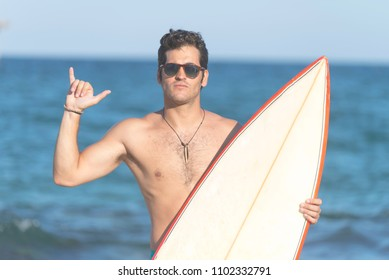 Surfer man holding surfboard doing shaka hand sign