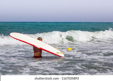 Surfer man holds his surfboard above his head in the waves of the sea