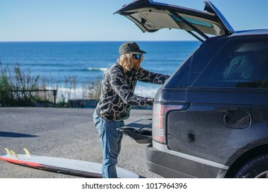 surfer man with long white hair in a cap and sunglasses with a surfboard. returns after surfing, folds the surfboard into the car. Nazare, Portugal.