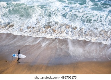 surfer man on the beach with turquoise-white water wave in the sea from top view at Bells beach, Torquay, Australia