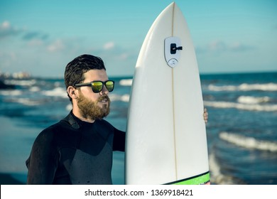 Surfer man portrait with sunglasses and holding a white surf board.He has a black surf suit.Sport concept