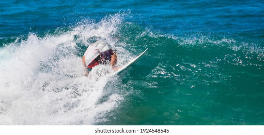 Surfer maneuvering on the wave.