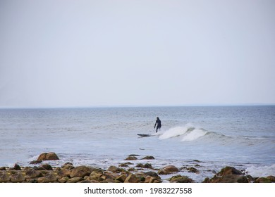 Surfer near the waves in the ocean in the summer