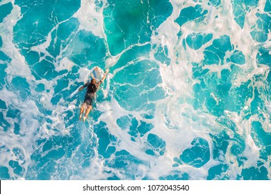 Surfer in the ocean, top view