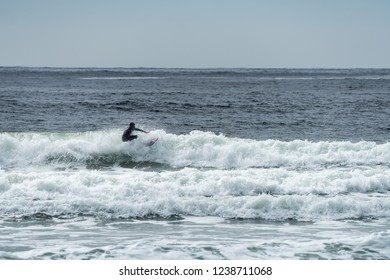 A surfer off the coast of Vancouver Island catching a wave at Chesterman Beach near Tofino, British Columbia Canada