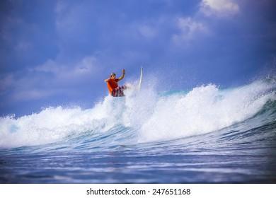 Surfer on Amazing Blue Wave, Bali island.