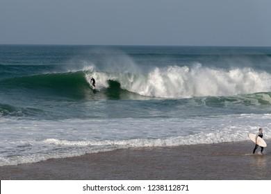 Surfer on Atlantic ocean wave , Nazare , Portugal.